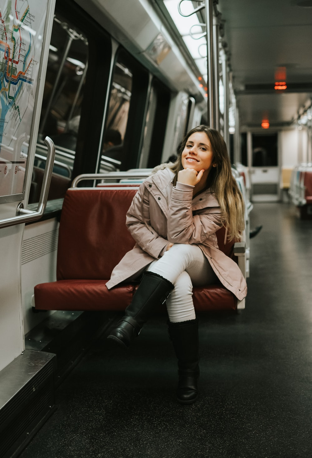 woman in coat sitting on train bench