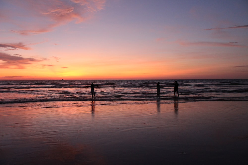 three people on seashore during golden hour