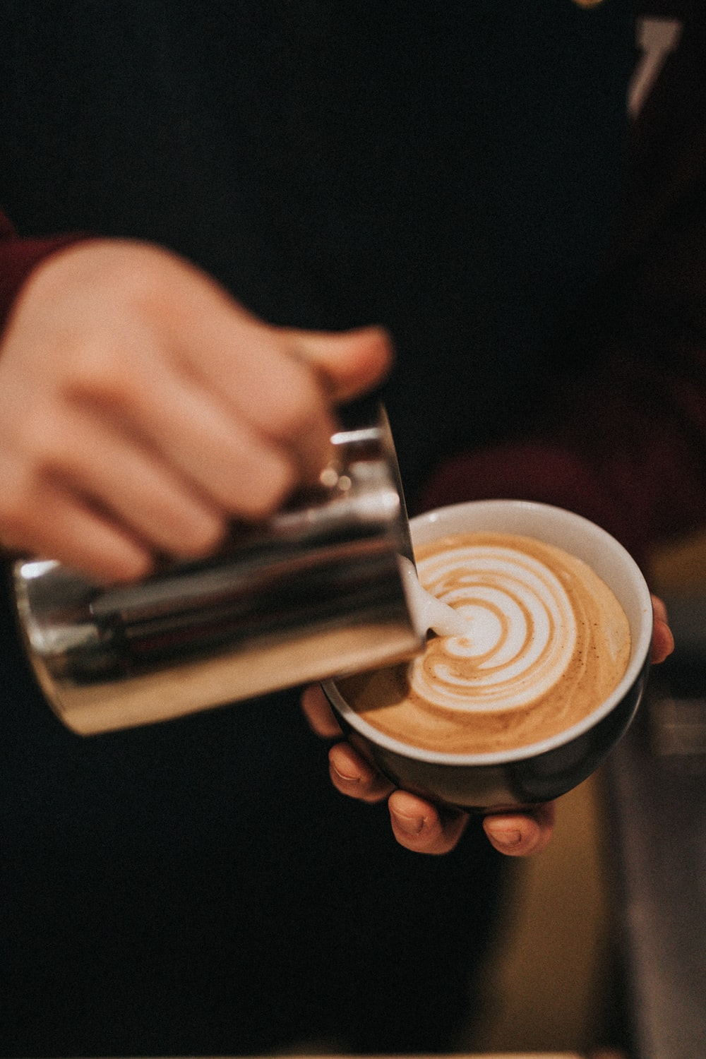 person pouring latte in mug