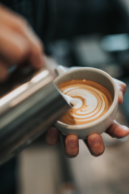 shallow focus photo of latte on white ceramic mug