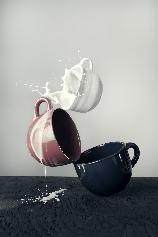 white mug spilling milk on brown and black mugs