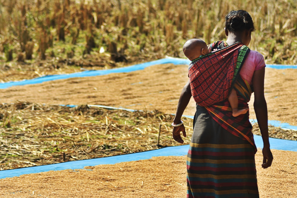 woman carrying child through sling while drying seeds