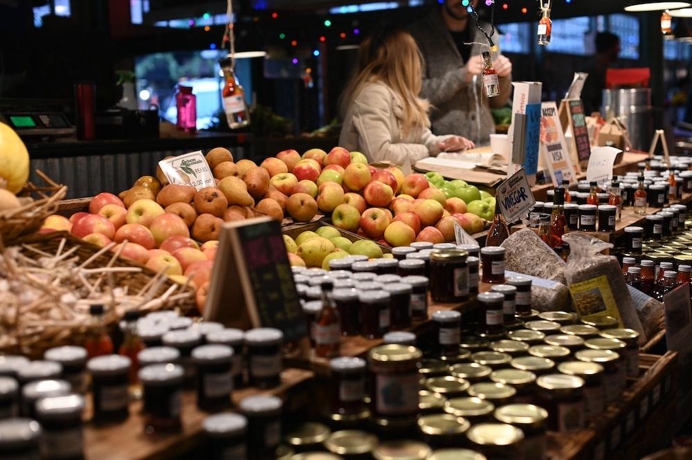 pile of apples in basket beside jars