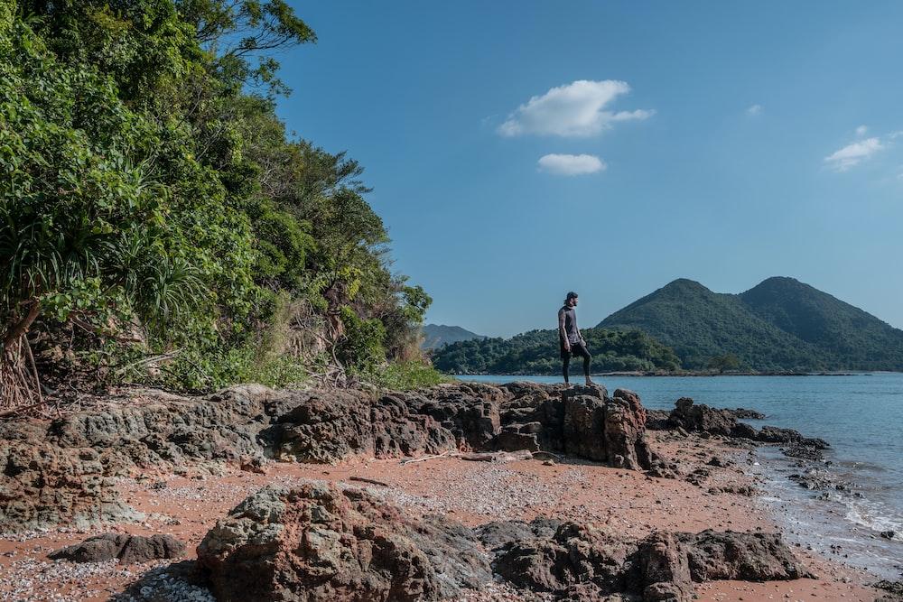 man sanding on boulder facing ocean under blue sky