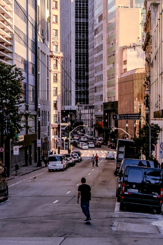 man skating on road between buildings