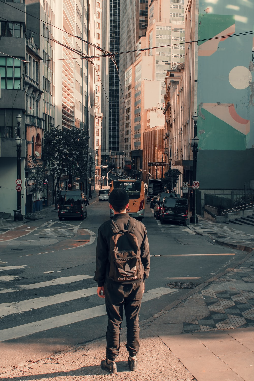 man carrying backpack standing on street