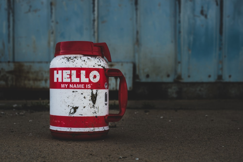 selective focus photography of white and red Hello printed bottle