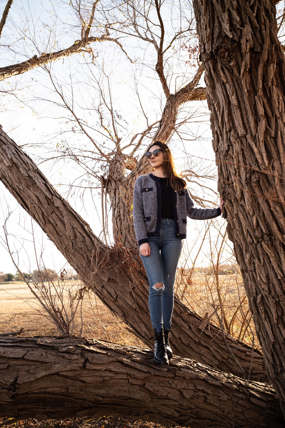 woman standing on tree branch during day