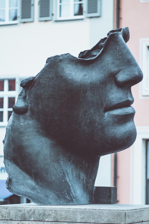 human head statue near buildings