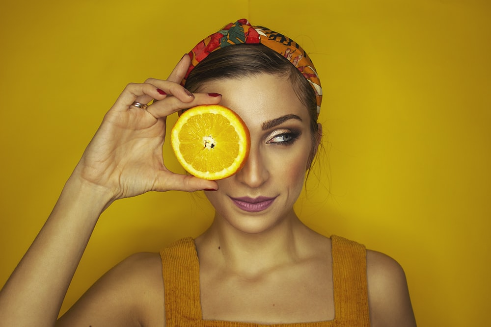 woman covering her right eye with orange slice