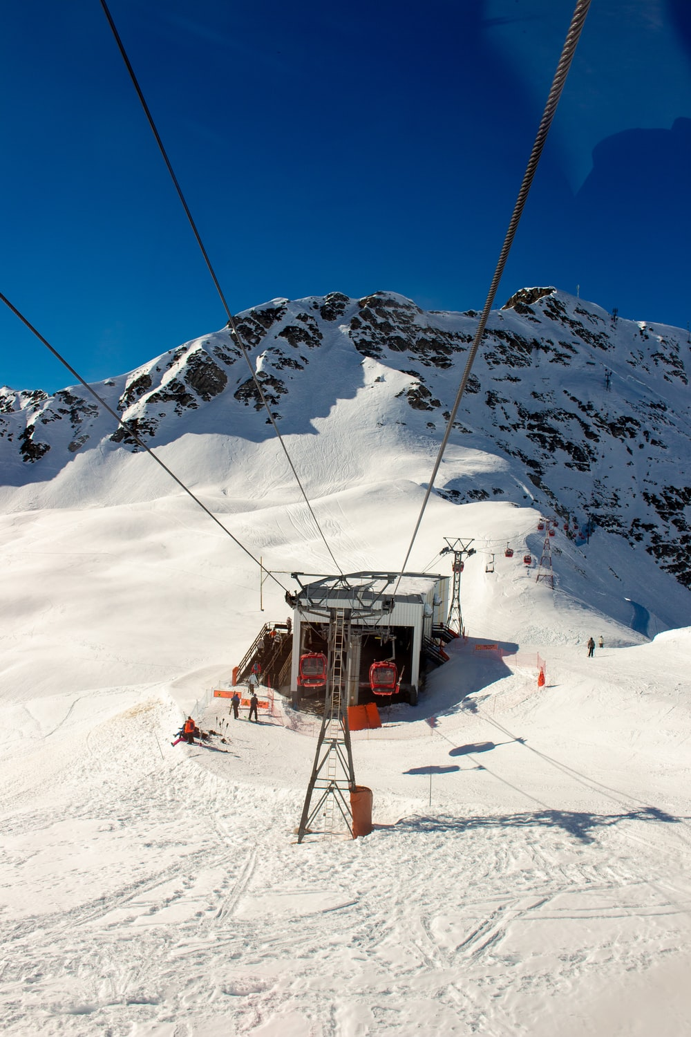 cable car in a snowy mountain under a calm blue sky during daytime
