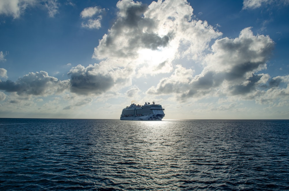 white cruise ship on blue sea under white and blue sky
