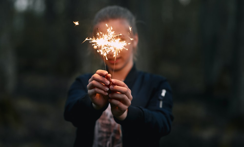 woman holding two lighted sparklers