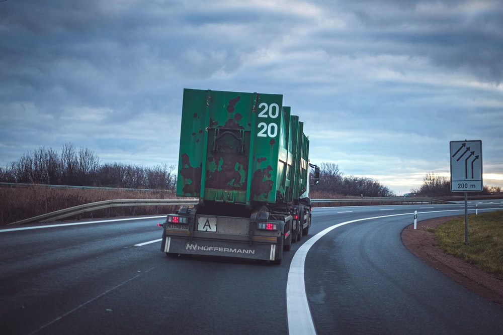 green freight truck passing by a winding road