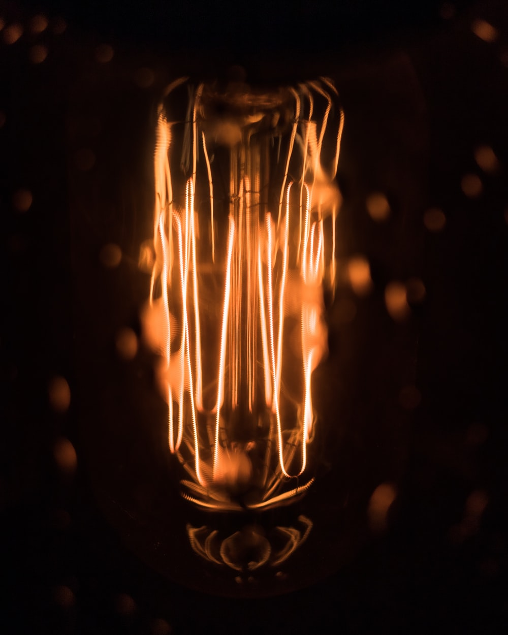 macro photography of lighted orange bulb