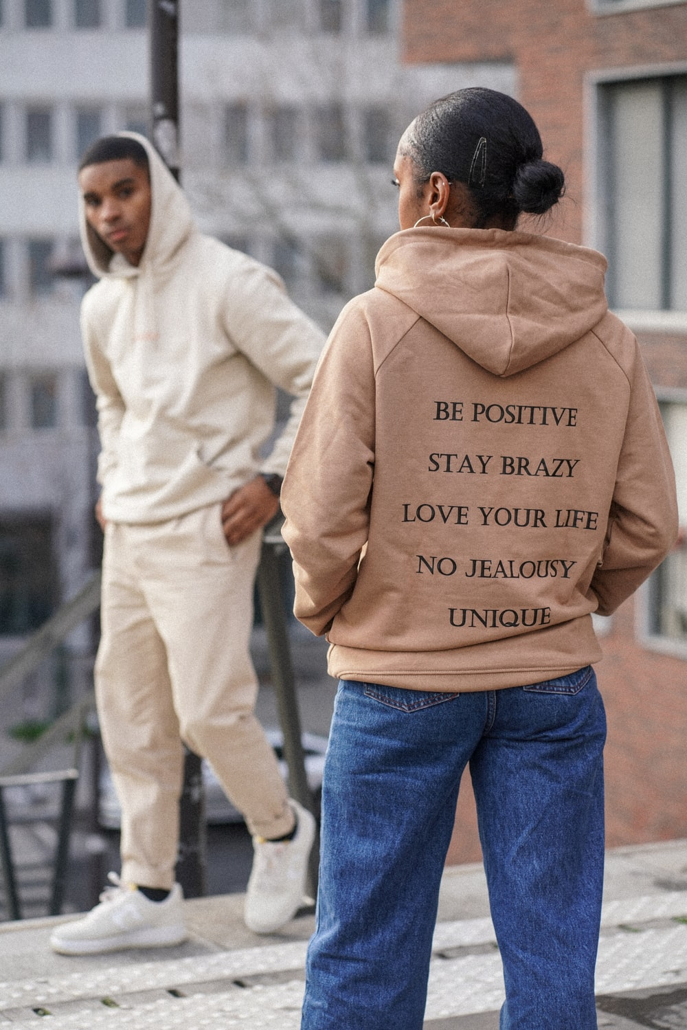 selective focus photography of woman in brown hoodie in front of man in white hoodie