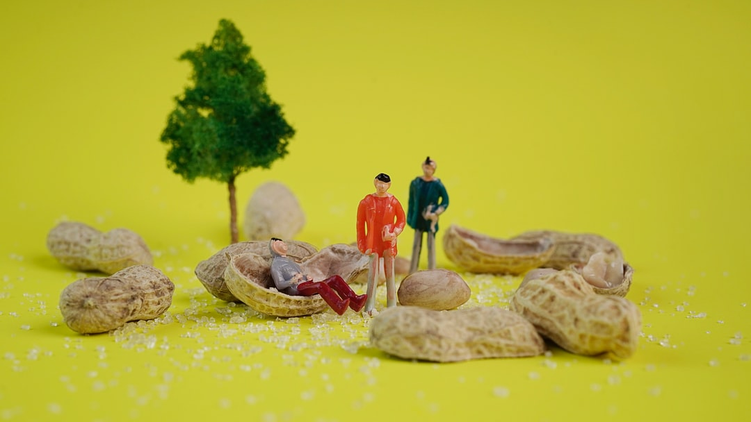 Creative concept with miniature people. people sit on peanut as a bench