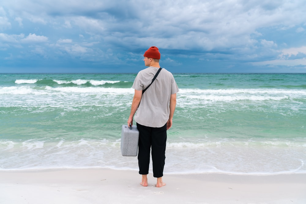 man carrying plastic case standing on seashore during day