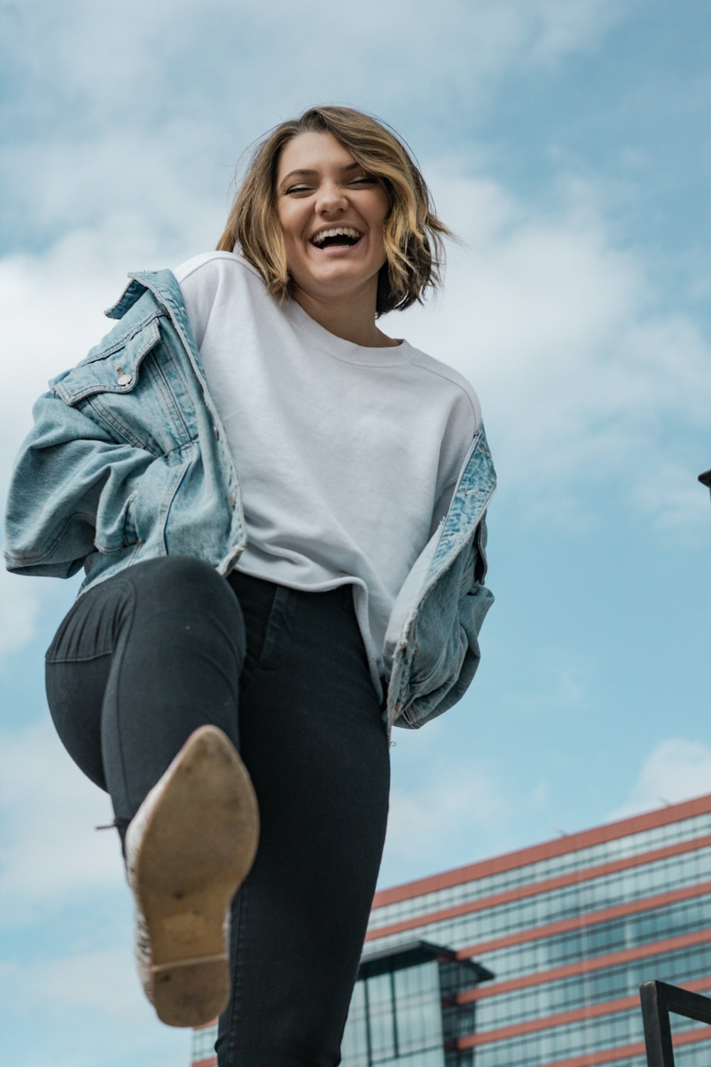 woman wearing white crew-neck t-shirt and blue denim jacket laughing while lifting right leg