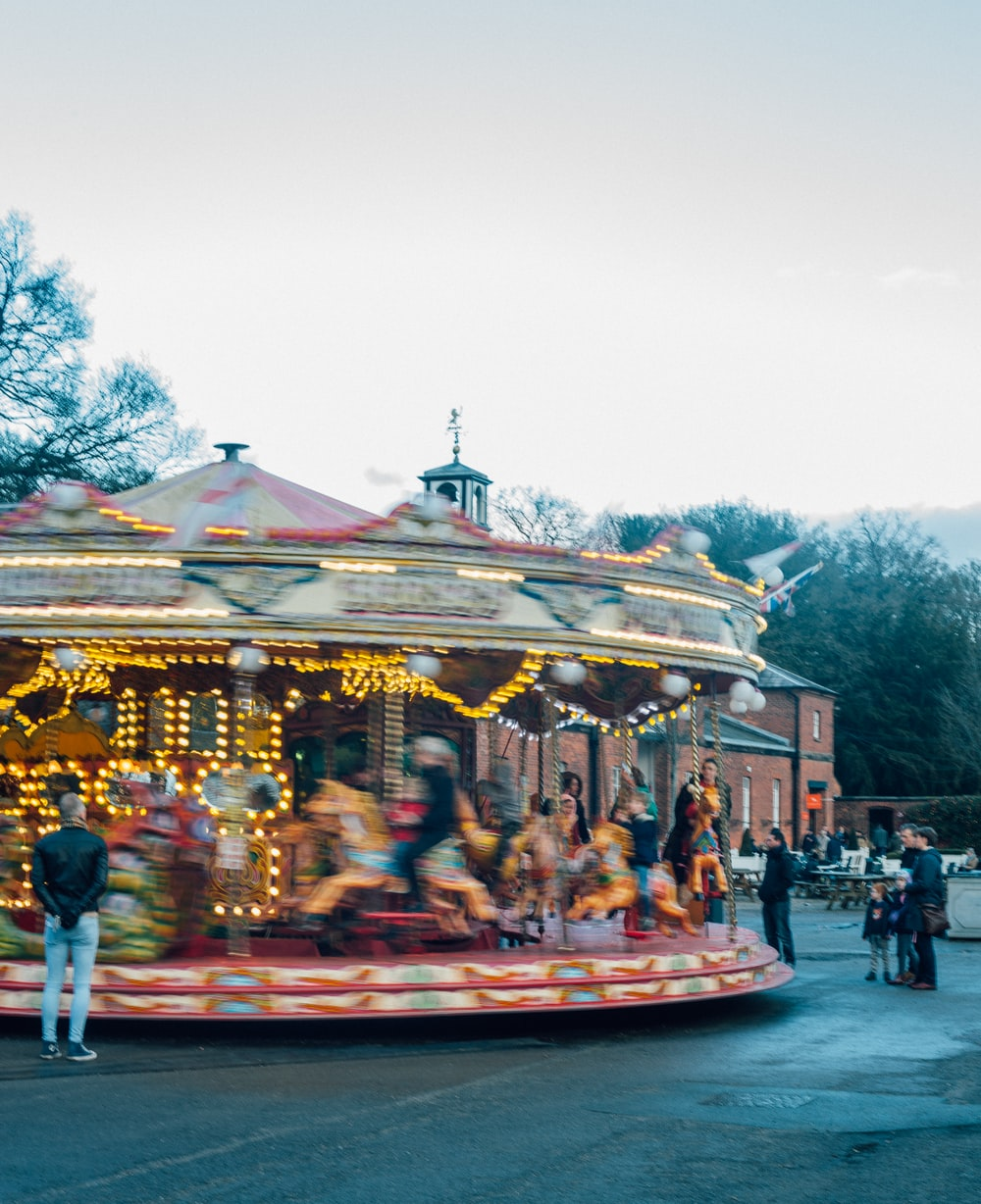 time-lapse photography of a spinning carousel under a calm blue sky