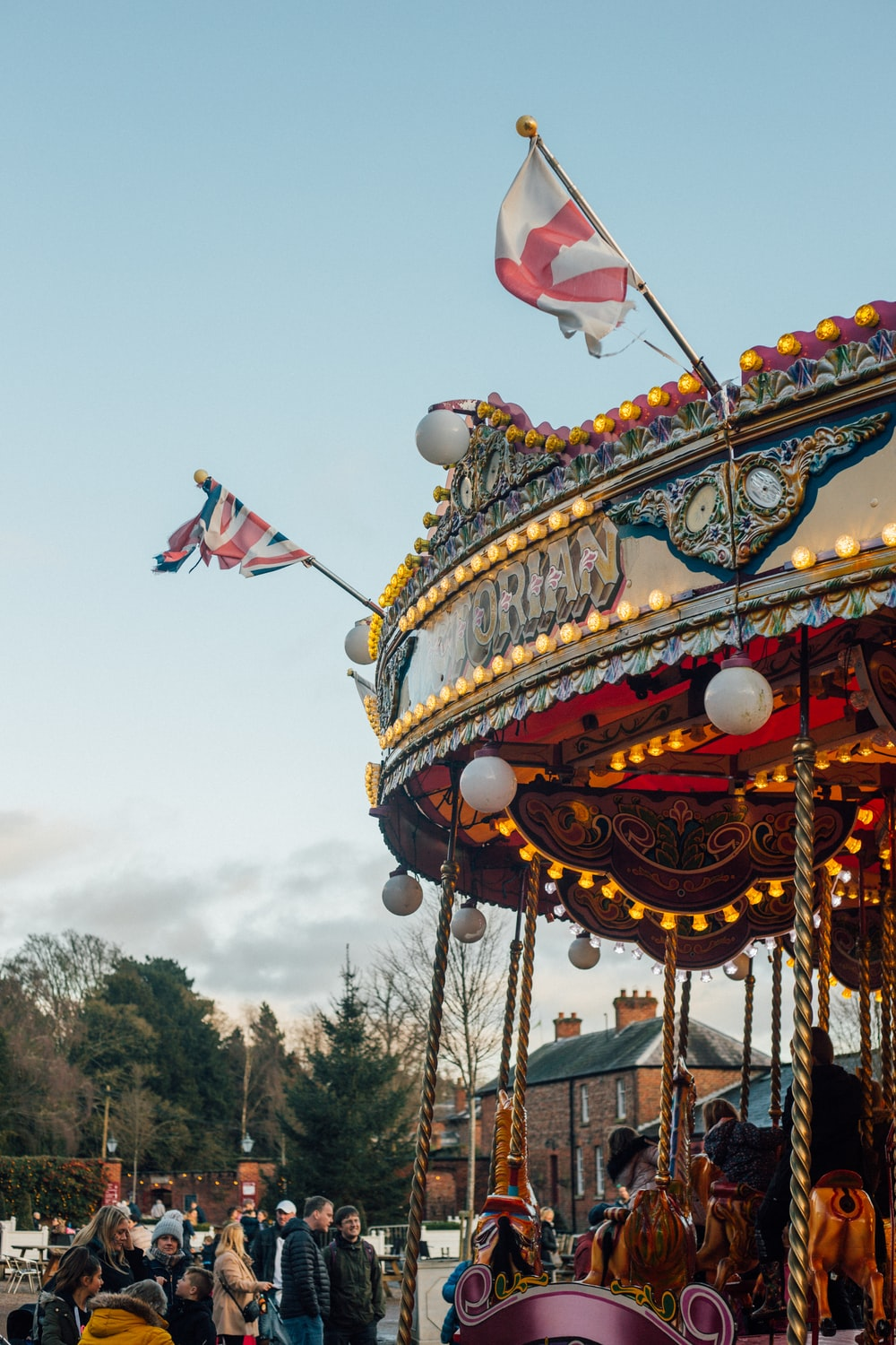 people around a carousel under a calm blue sky during daytime