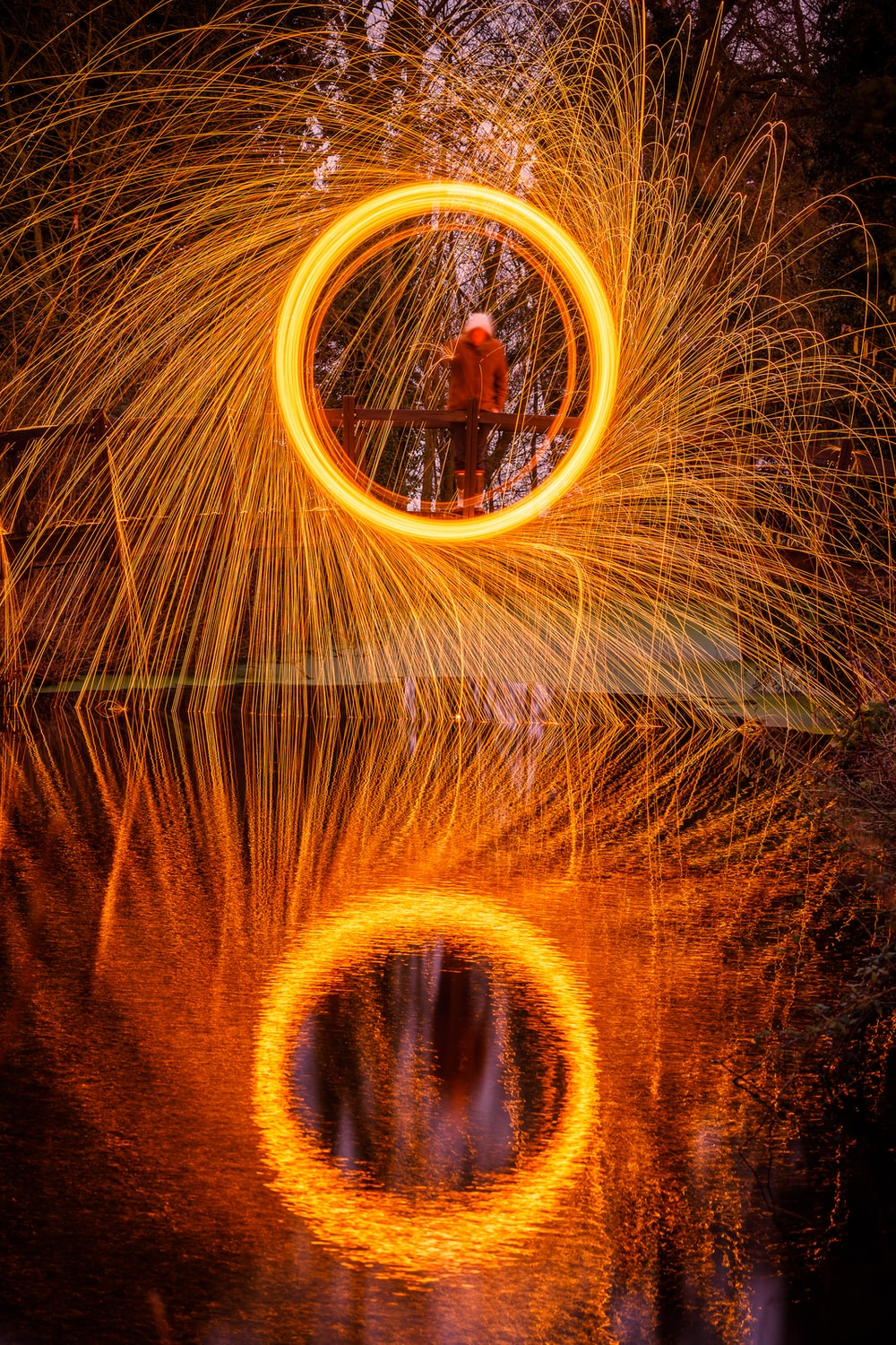 person standing on bridge steel wool photography