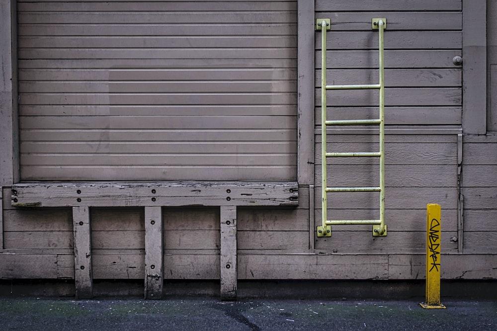green metal ladder on wall