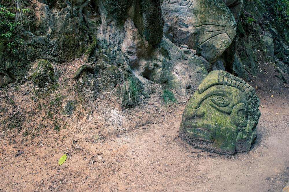 green concrete head statue on pathway