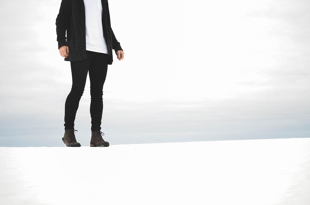 黒のズボンと黒のジャケットを着ている人