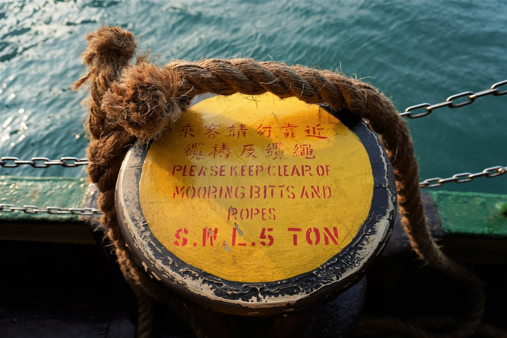 brown jute rope over a round yellow metal signage