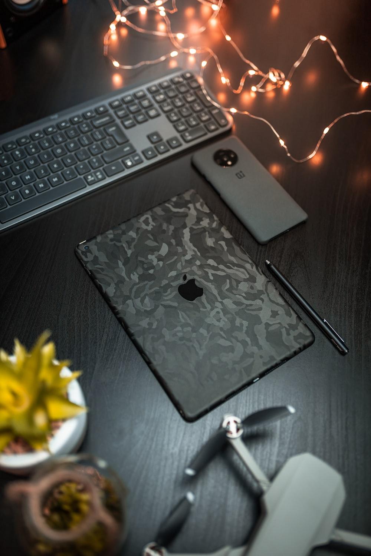 black iPad near black pen, black computer keyboard, and gray Android smartphone