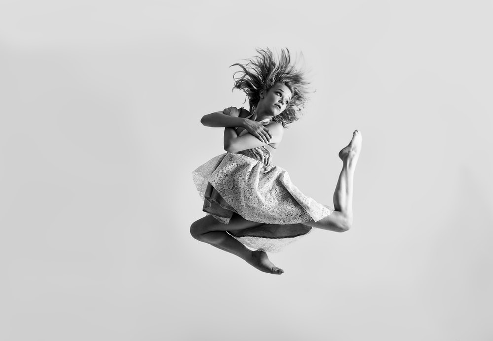time-lapse grayscale photography of woman jumping on air