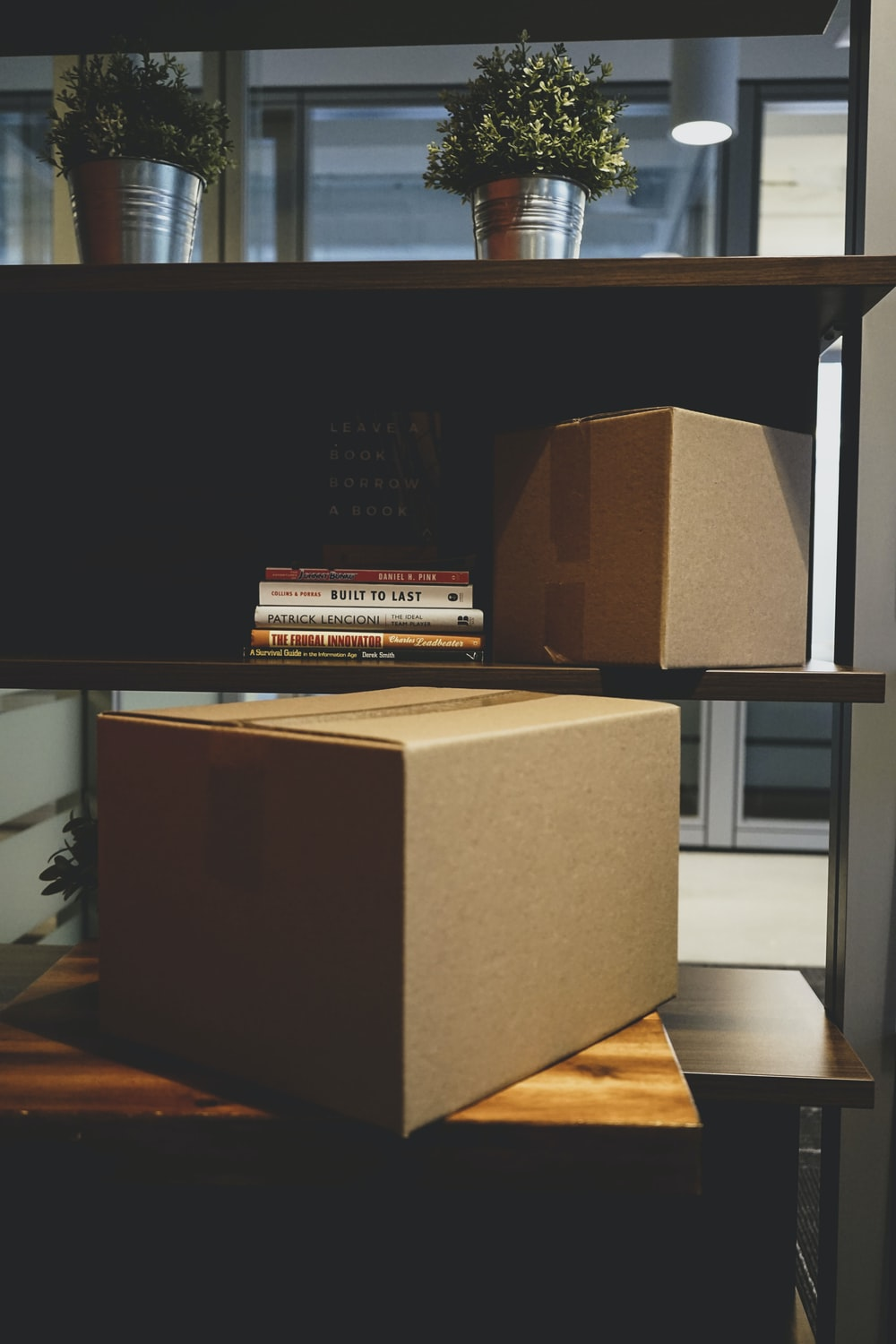 two brown boxes and DVD cases on rack