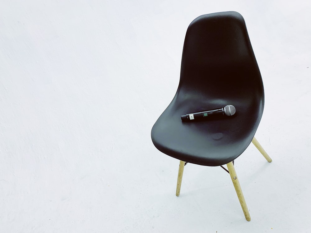 black wireless microphone on black armless chair