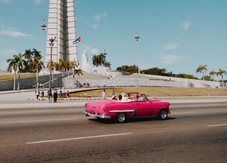 pink coupe passing by monument during daytime