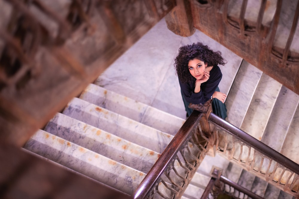 shallow focus photo of woman standing on stairs