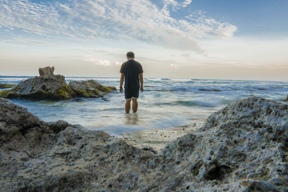 man standing on seashore near rocks