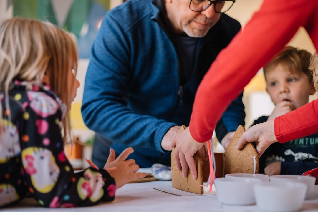 Kids With Grandparents Making A Gingerbread House - unsplash