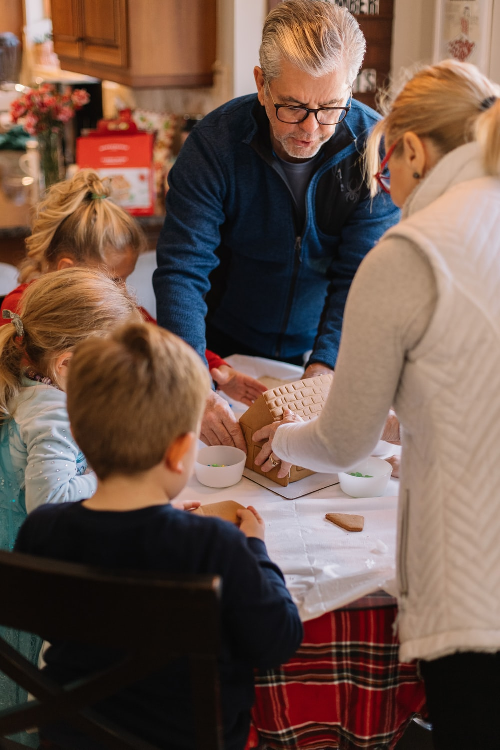 two women standing and three children sitting while preparing gingerbread house