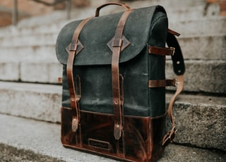 brown and black leather bucket backpack on concrete staircase
