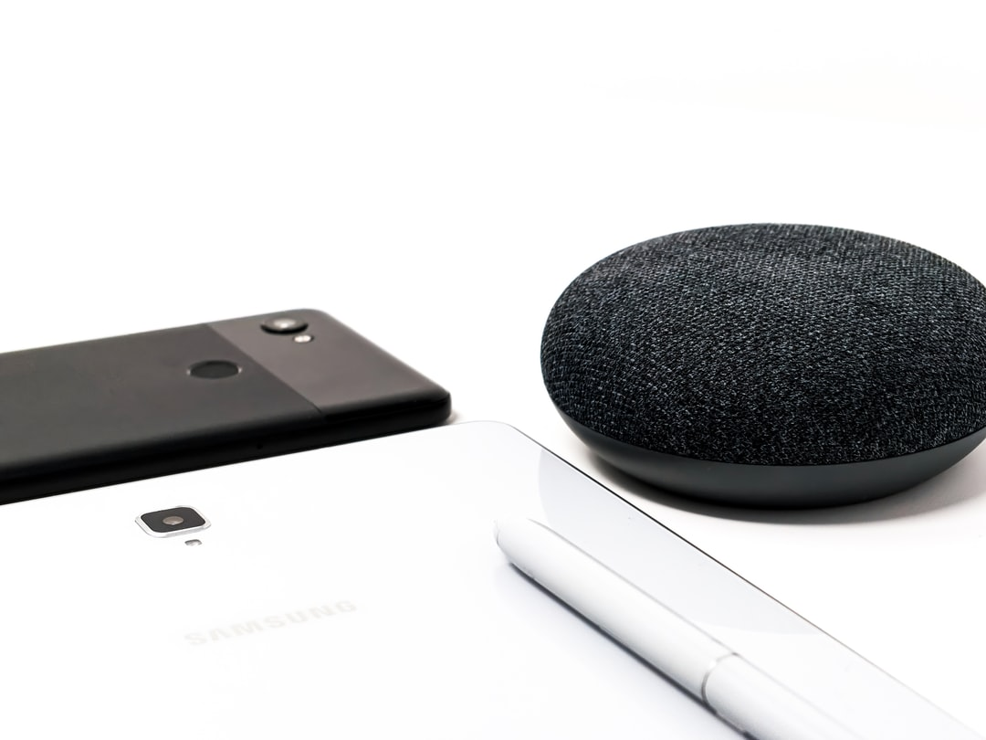Black Phone, white tablet, white pen and Black Google home mini on a white table.
