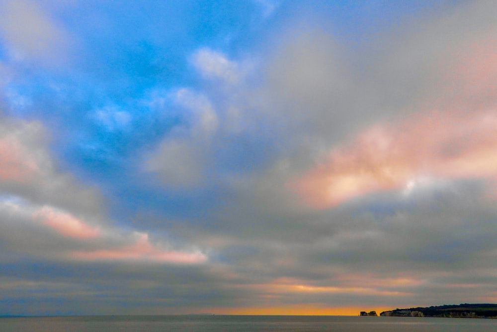 body of water under cloudy sky during golden hour