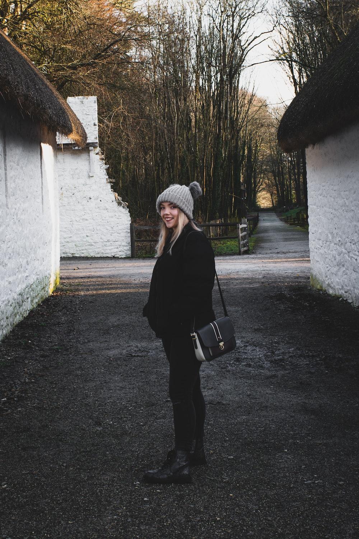 smiling woman wearing black jacket and pants carrying crossbody bag