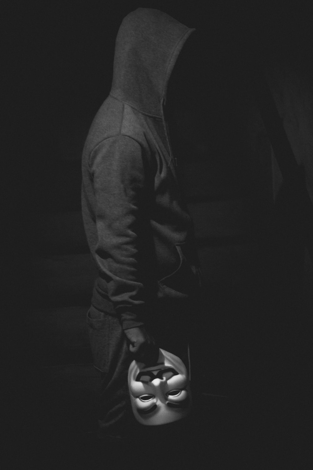 standing man holding Guy Fawkes mask