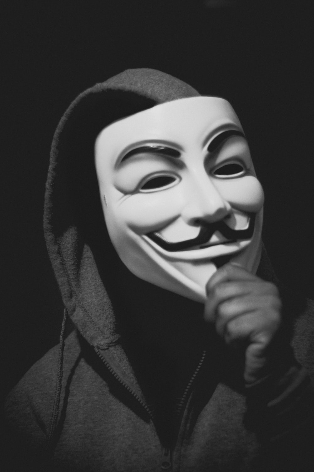 person holding Guy Fawkes mask