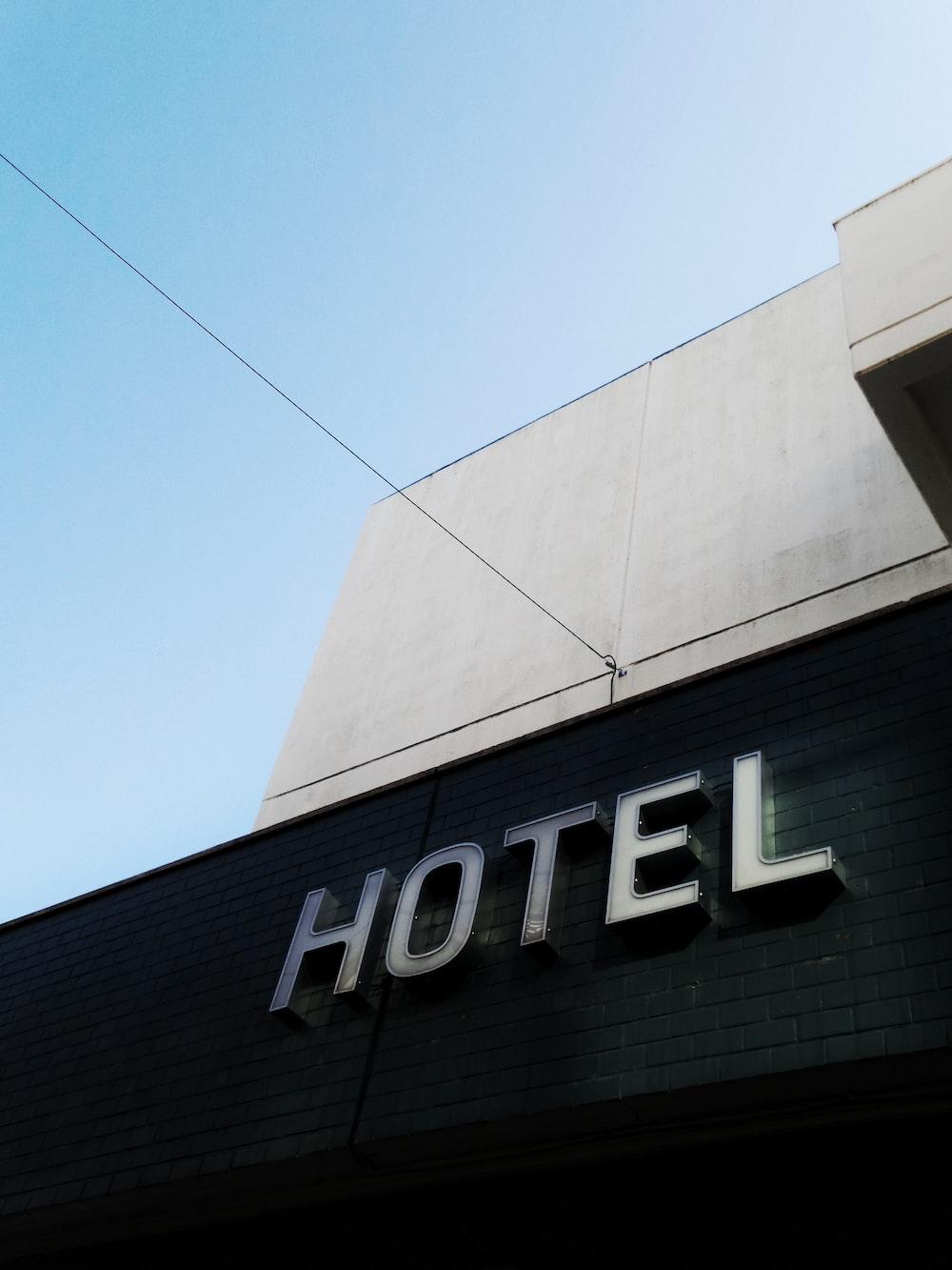 black and white concrete hotel building under a calm blue sky