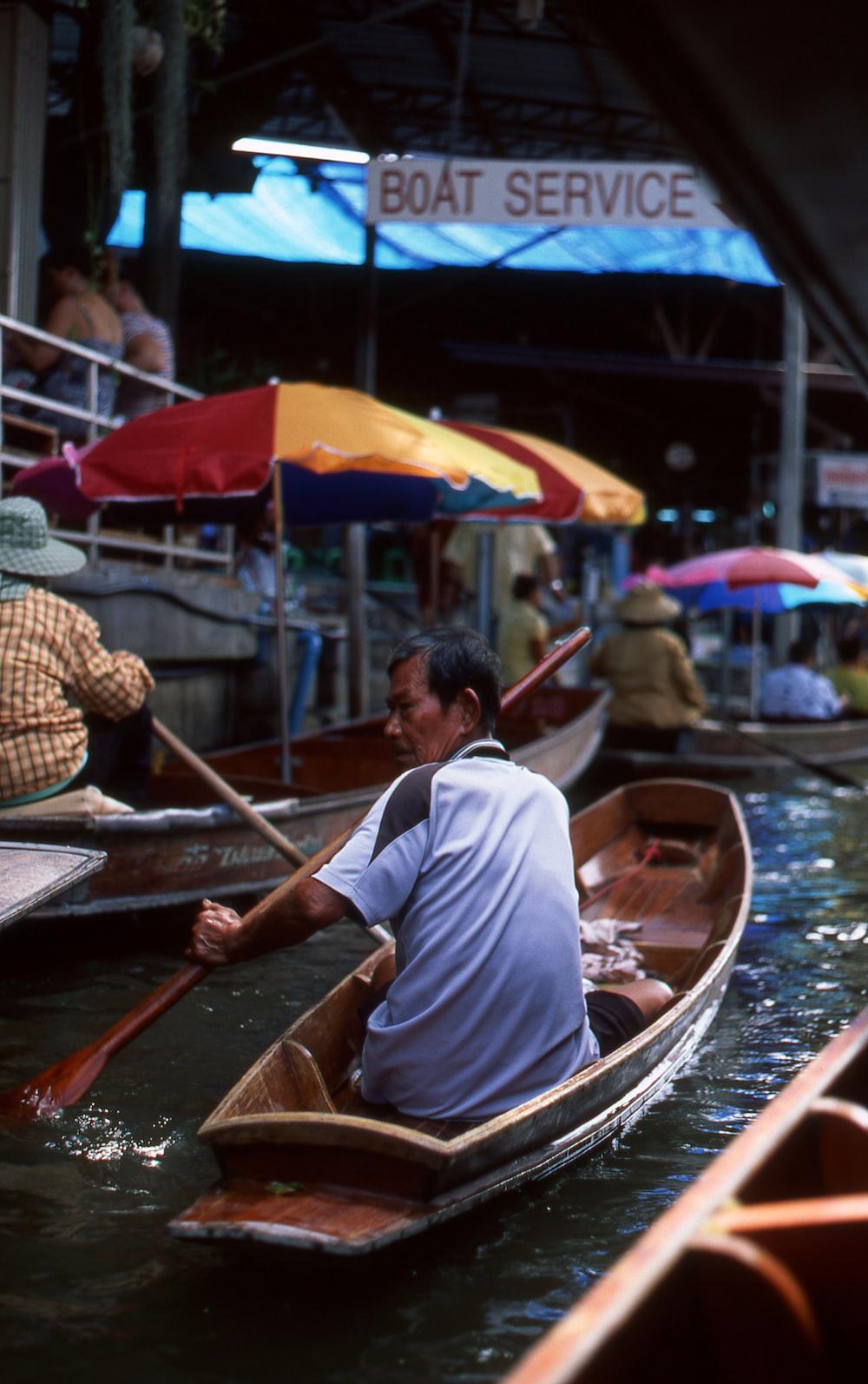 man wearing blue shirt riding on boat