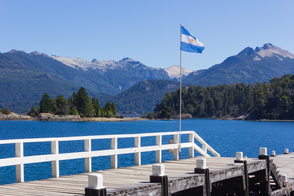 white and blue flag on wooden dock near body of water during daytime