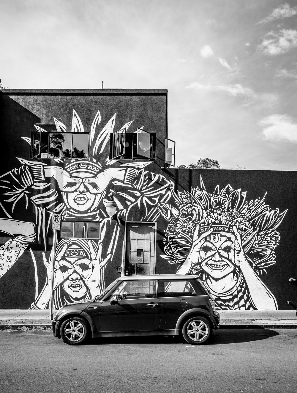 parked car near building with murals