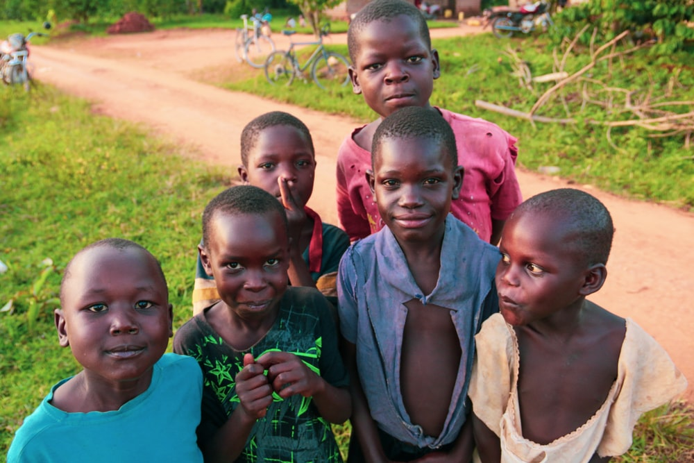 six children standing near rough road